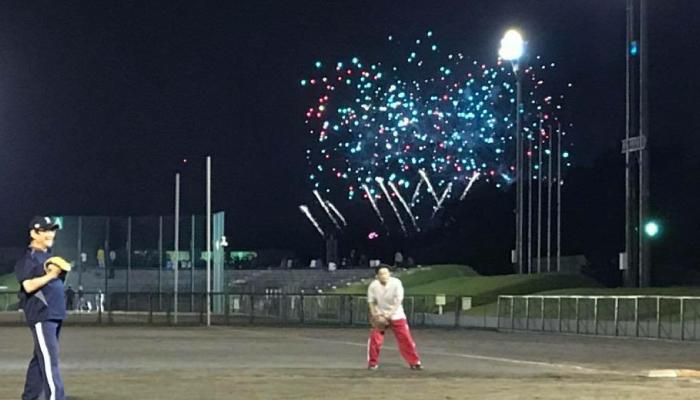 ソフトボールのナイター試合風景その2後ろで花火が上がってる